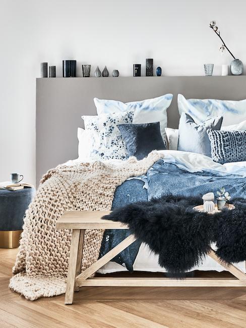 Cama decorada con mantas en tonos distintos de azul petróleo y gris