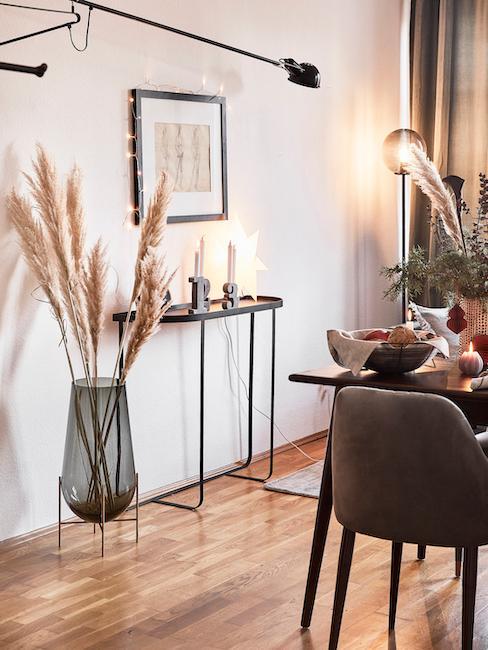 Gerookte glazen vaas Echassé versierd met pampagras voor zwart dressoir en foto in de eetkamer.