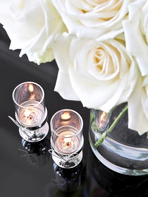Zbliżenie na białe róże i świeczniki w prezencie dla dziewczyny