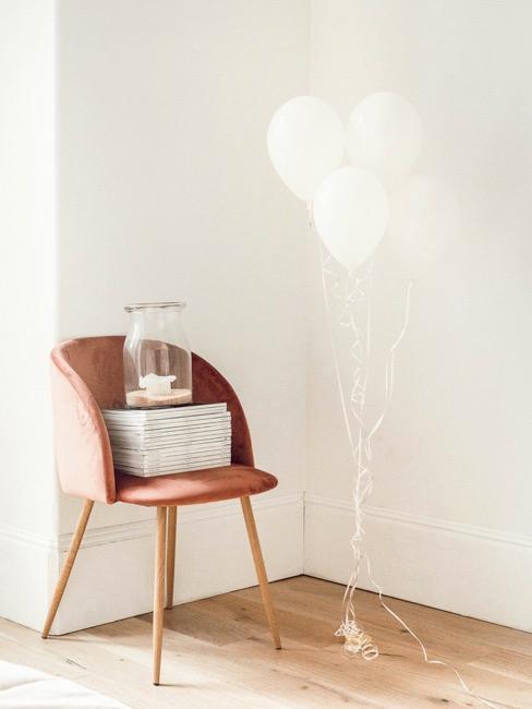 silla de terciopelo con globos de fiesta blancos