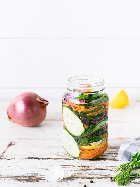 Salat im Glas auf einem weißen Holztisch, daneben eine Zwiebel