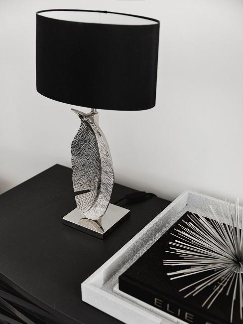 Deko-Lampe mit Lampenfuß in Form einer Feder auf einer Kommode
