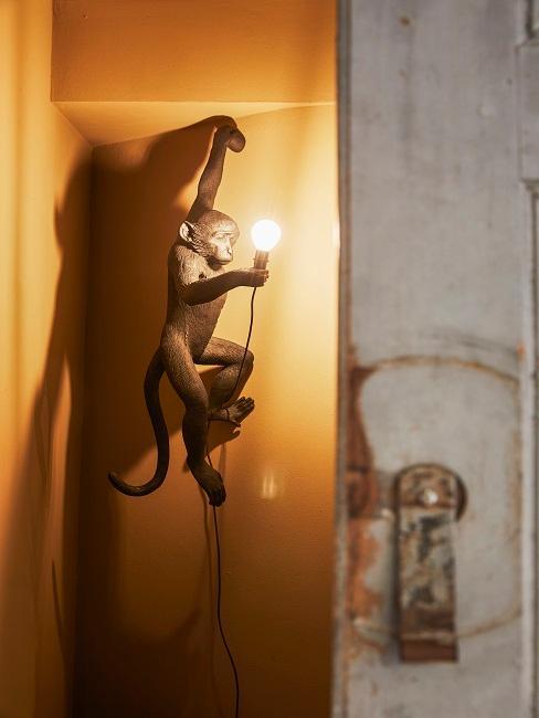 Affenlampe in Schwarz an der Wand hängend