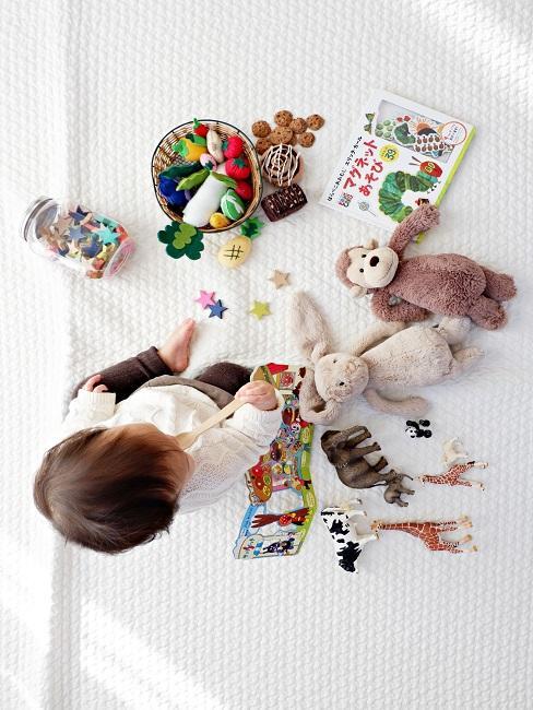 Kind op een wit vloerkleed met veel speelgoed eromheen