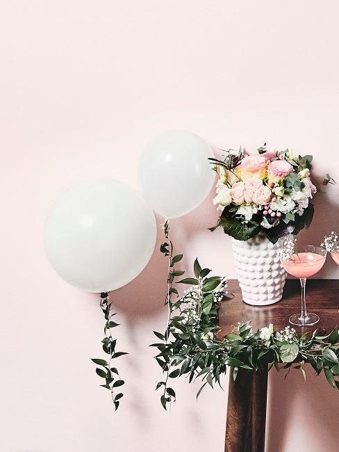 Luftballons in Weiß an einen Tisch mit Blumendeko gebunden