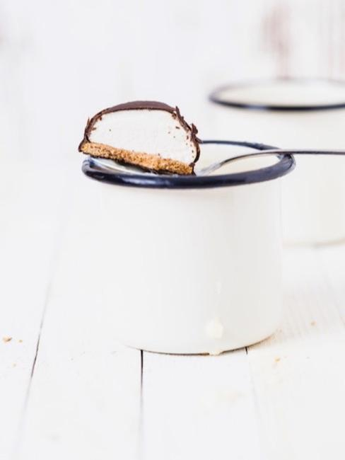 close-up tafel met wit geglazuurde beker en koek