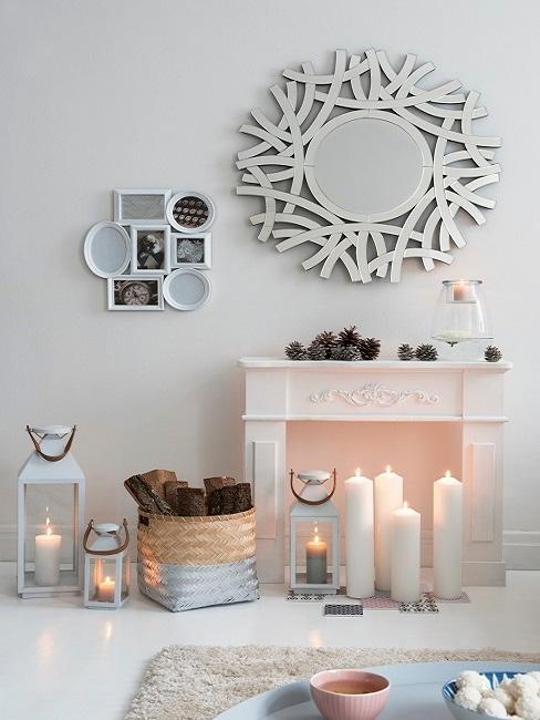 Biały kominek z kilkoma białymi świecami oraz latarenkami o różnych rozmiarach.