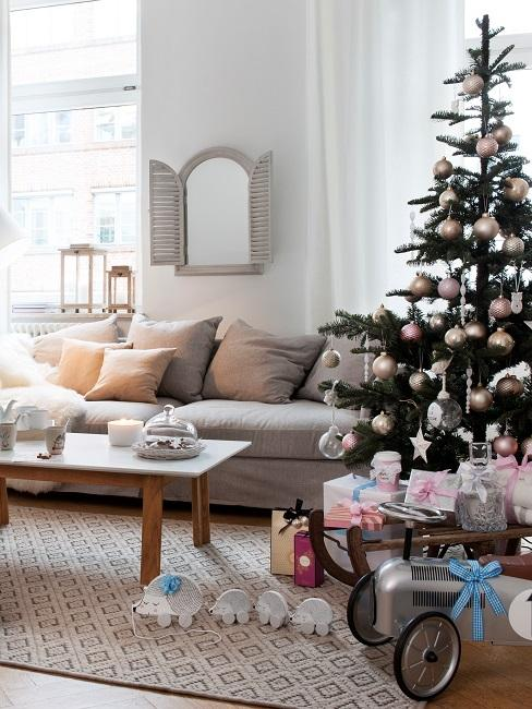 Salón con árbol de Navidad, sofá beige y regalos