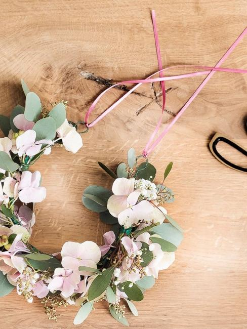 Rosa Band an die Enden des Blumenkranzes wickeln