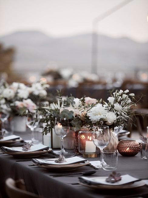 Gedeckter Hochzeitstisch Outdoor mit vielen Kerzen und Blumen als Tischdeko