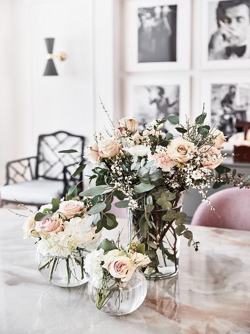 Drei Vasen mit hellen Rosen auf dem Esstisch