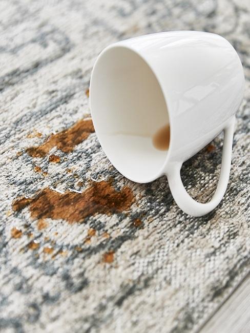 Rozlana filiżanka kawy na jasnym dywanie.