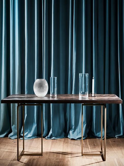Ein Esstisch aus dunklem Holz mit Vasen vor einem Vorhang in Petrol