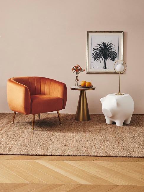 Sessel in Kurkuma auf einem Teppich neben einem goldfarbenem Couchtisch und einem Deko-Schwein