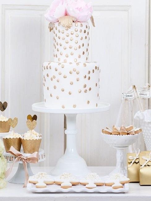 Verzierte Hochzeitstorte in Gold-Weiß-Rosa, daneben eine Candy Bar