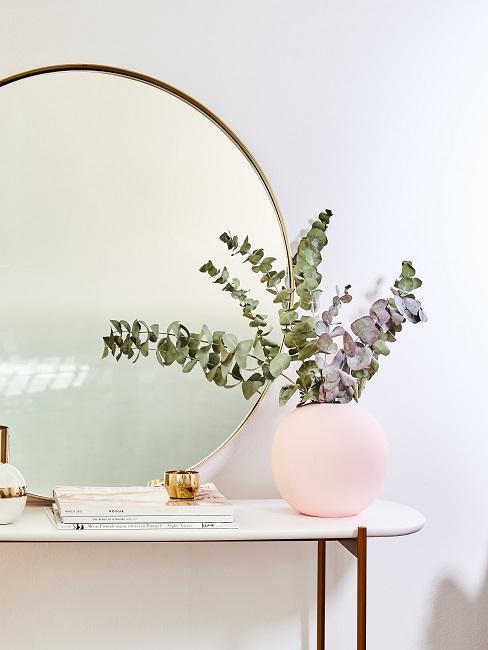 Eukalyptus Zweige in einer rosa Kugelvase auf einer Konsole mit einem runden Spiegel mit goldenem Rahmen.