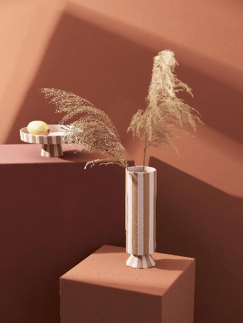 Gestreifte Vase auf Tisch und vor Hintergrund in Terracotta Farbe