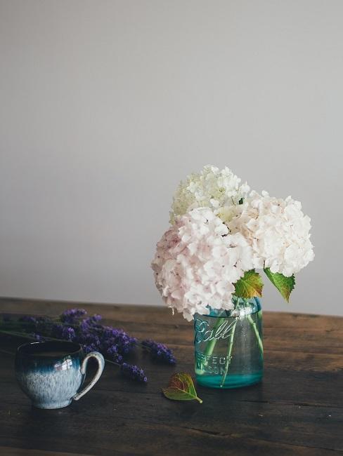 Holztisch mit einer Vase mit Blumen, daneben eine Pflanze und Blumdeko auf dem Tisch liegend