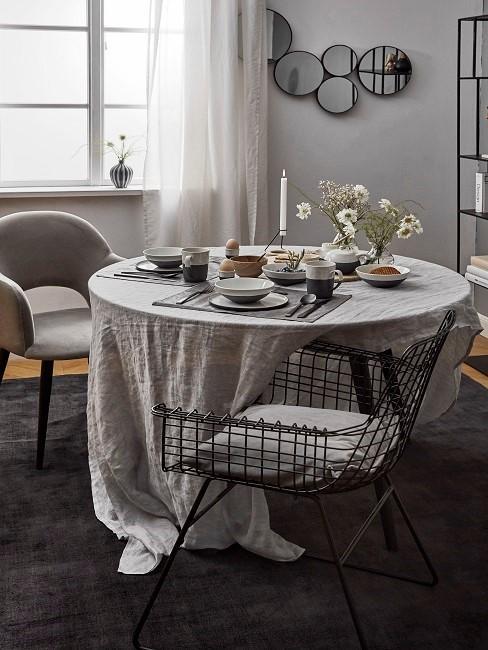 Esszimmer skandinavisch mit weißem, runden tisch und schwarzem Teppich