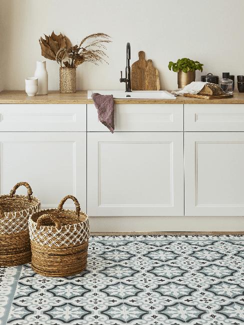Küche mit weißen Schränken und Körben als Deko
