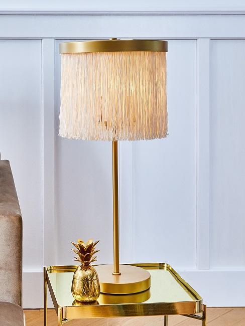 Mid Century modern Lampe auf goldenem Tisch neben kleiner goldener Ananas