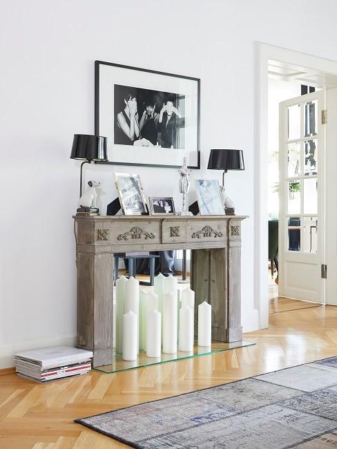 Kamin-Attrappe mit weißen Kerzen und dekoriert mit Lampen und Bildern