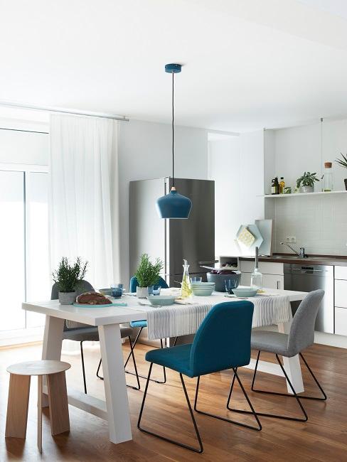 Wohnküche mit weißem Tisch und blauen Stühlen