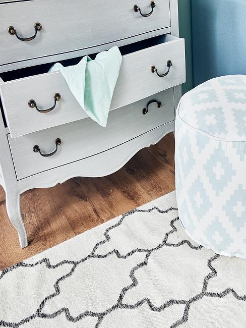 Weiße Holzkommode im nostalgischen Look auf Holzboden, davor ein gemusterter Teppich und ein Pouf