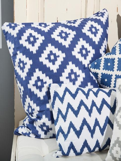 Weiß-Blau gemusterte Boho Kissen auf einem hellen Bett aus Holz