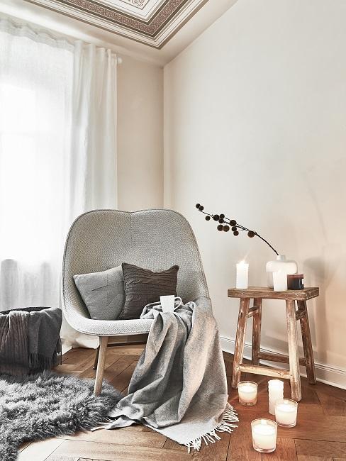 Sessel mit zwei Kissen und einer Decke, daneben auf einem Holz-Beistelltisch und auf dem Boden Kerzen zur Deko