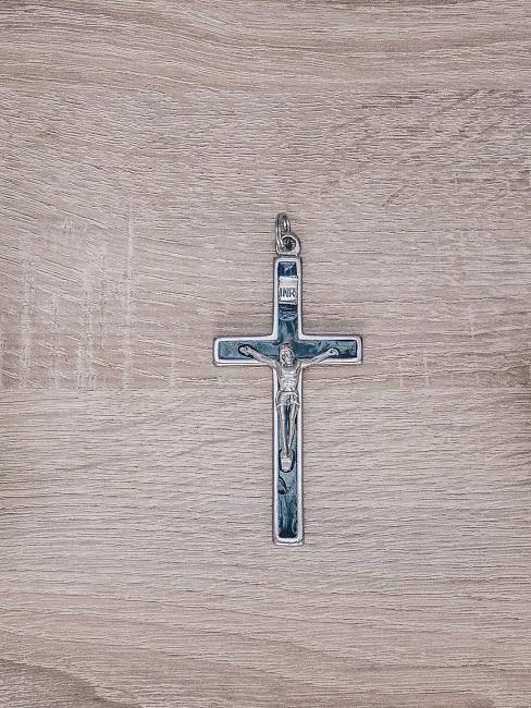 Kreuzanhänger als Glaubenssymbol auf Holztisch