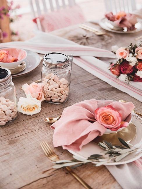 Ein Holztisch mit Deko in Rosa, vor allem Rosen