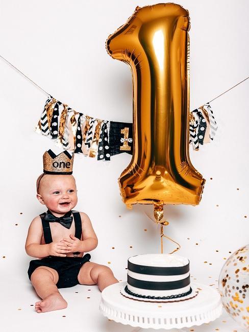 Geschenke zum 1. Geburtstag Baby neben Kuchen und Luftballon