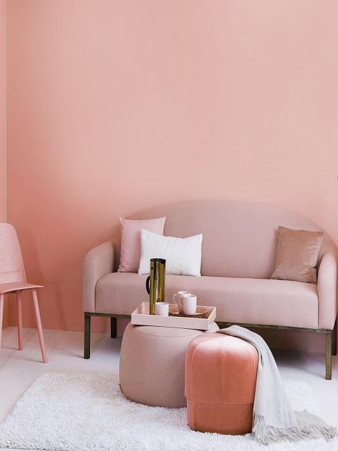 Ein kleines Sofa in Rosa vor einer Wand in Rosa mit hellem Teppich und einem Pouf mit Tablett anstatt eines Couchtischs