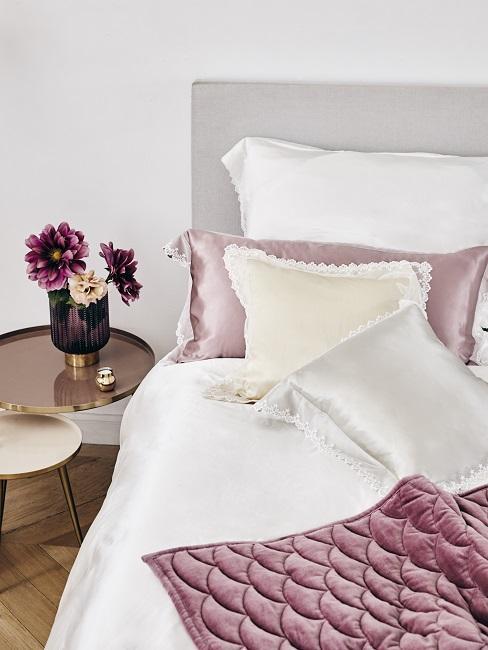 Bett in Weiß und Pastelltönen mit Bettwäsche Material aus sommerlicher Seide