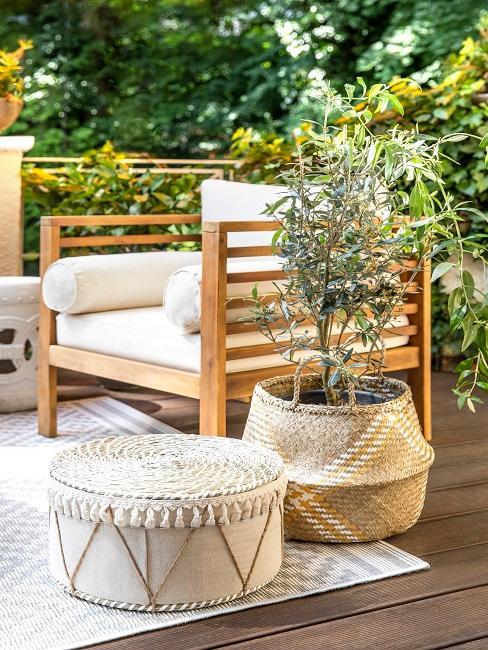 Kolonialstil Stuhl mit weißen Kissen neben Dekokörben und Pflanze