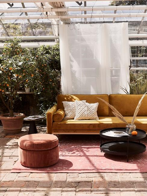 Gelbes Samtsofa im Outdoorbereich mit Pflanzen und rotem Pouf
