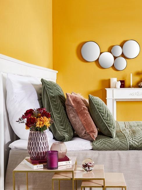 Warme Wandfarbe Gelb in Schlafzimmer mit grünen Kissen