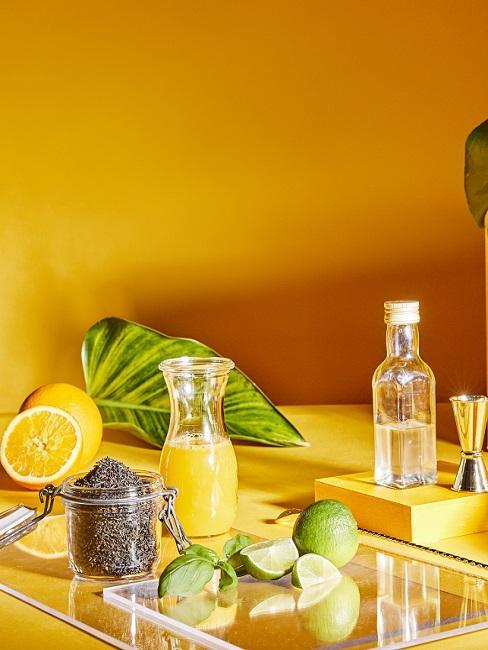 Dunkelgelbe Wand hinter Zitronen und Gläsern