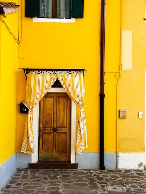 Gelbe Wandfarbe an Hauswand mit Holztür