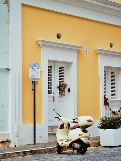 Gelbe Hauswand mit weißen Türen und Fenstern