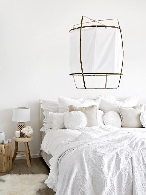 Schlafzimmer mit weißer Bettwäsche und weißer Lampe