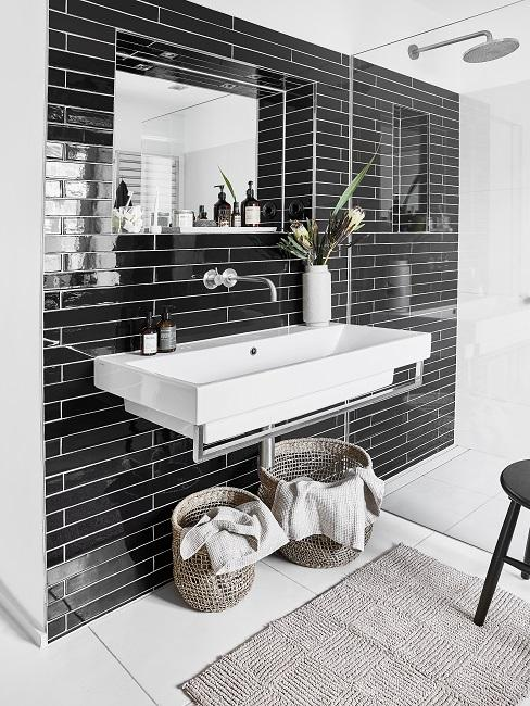 Badezimmer mit schwarzen Fliesen, weißem Waschbecken, Dusche und Dekokörbe