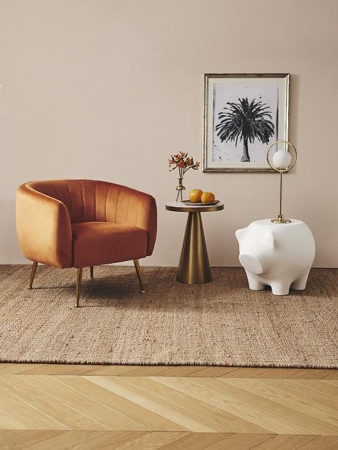 Beigefarbene Wand hinter orangem Sessel, goldenem Beistelltisch und Tischleuchte