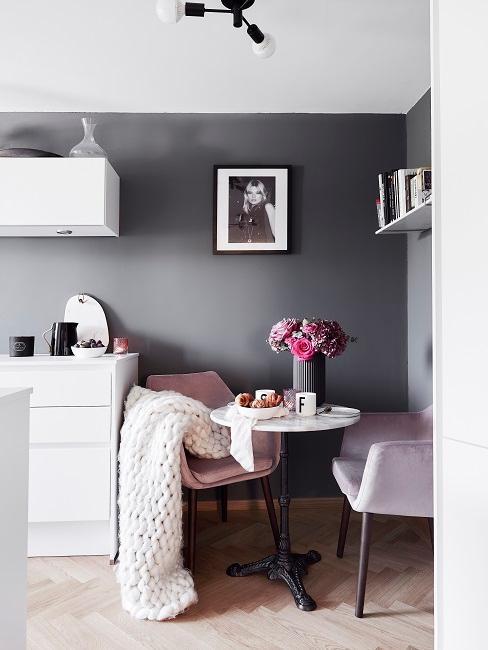 Dunkelgraue Wand in der Küche mit weißer Küchenzeile und rosa Stühlen