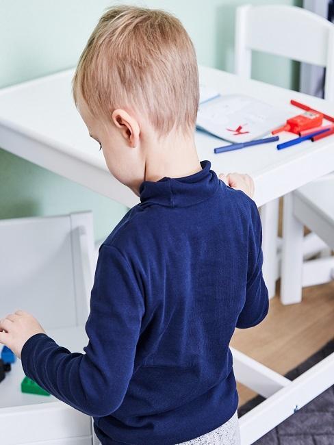 Junge steht vor Schreibtisch