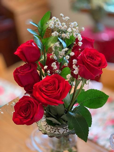 Rote Rosen mit Schleierkraut in Vase