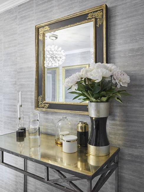 Weiße Rosen in großer Vase neben Deko auf goldener Konsole