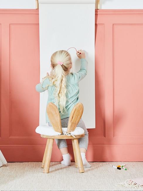 Mädchen mal auf langem Papier an der Wand
