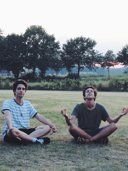 dos chicos haciendo ejercicios de respiracion en la naturaleza
